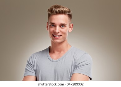 Portrait of smiling young man on grey background