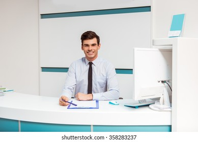 Portrait of smiling young man with receptionist in dentist office