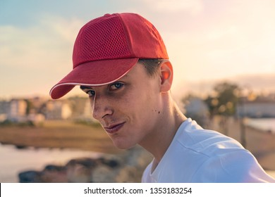 portrait of a smiling young man with red baseball cap