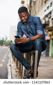 Portrait of a smiling young man sitting with a mobile phone on an iron bar in the street