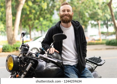 Portrait of smiling young man sitting on his motorcycle. Happy biker posing with motorbike outdoors. Biker lifestyle concept