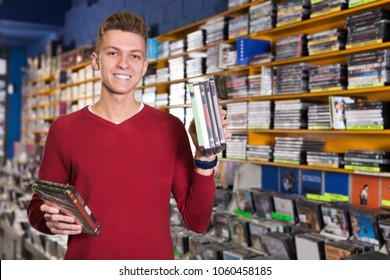 Portrait of smiling young man with stack of DVDs in hands in store