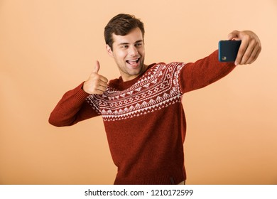 Portrait a smiling young man standing isolated over beige background, taking selfie with mobile phonem, showing thumbs up