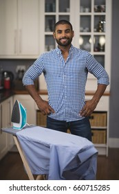 Portrait of smiling young man standing by iron on board in kitchen at home