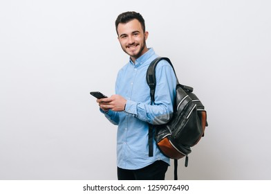 Portrait of smiling young man texting and wearing a backpack