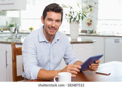 Portrait of a smiling young man using digital tablet at home