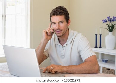 Portrait of a smiling young man using laptop and mobile phone at home