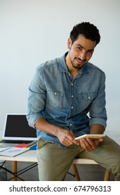 Portrait of smiling young man using digital tablet on desk at office