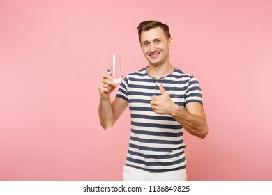 Portrait of smiling young man wearing striped t-shirt holding and drinking clear fresh pure water from glass isolated on trending pastel pink background. People sincere emotions lifestyle concept