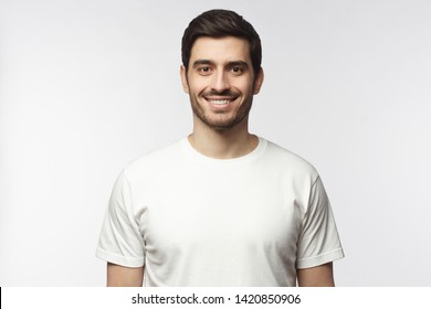 Portrait of smiling young man in white t-shirt looking at camera, isolated on gray background