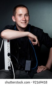 Portrait of a smiling young man in the wires on a dark background of the studio