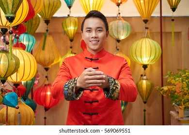 Portrait of smiling young man wishing you prosperity in new Year