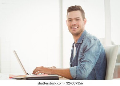 Portrait of smiling young man working on laptop while sitting at desk