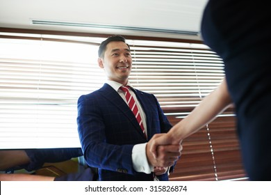 Portrait of a smiling young managing director shaking hands with his business partners while standing in office space interior, asian male entrepreneur enters into an agreement with his new partner