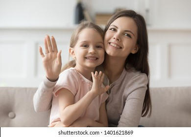 Portrait of smiling young mom hold hugging cute preschooler daughter look wave to camera, happy mother or nanny cuddle with little girl child shoot record video blog say hello to viewers