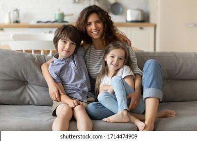 Portrait von lächelnden jungen Mama umarmen kleine Sohn Tochter, entspannen auf der Couch im Studio Wohnzimmer. Positive Babysitterin, kuschelend kleine Kinder Geschwister, sitzend auf Sofa, Blick auf Kamera.