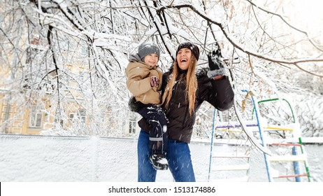 Portrait of smiling young mother in coat and hat with her pretty son in jacket playing with snow covered tree on the playground in the Park