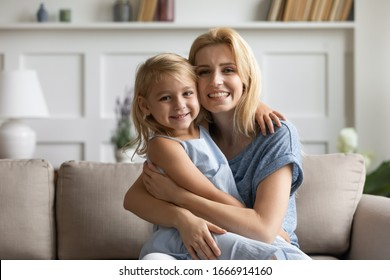 Portrait of smiling young mother and cute little preschooler daughter sit on couch in living room look at camera, happy mom and small girl child hug embrace relax on sofa at home, bonding concept