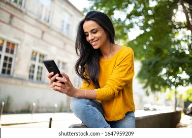 Portrait smiling young North African beautiful woman sitting outside in city looking at mobile phone