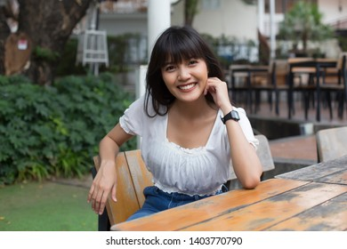 Portrait of smiling young pretty asian woman sitting in outdoor restaurant