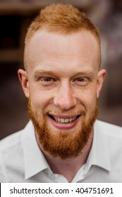 portrait of smiling young red hair man with beard vertical