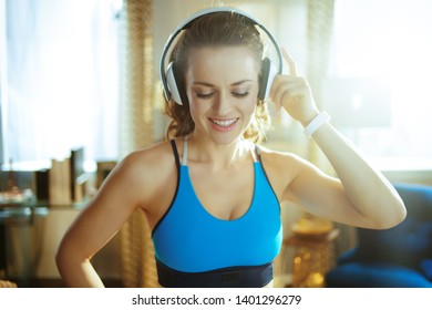 Portrait of smiling young sports woman in sport clothes listening to the music with headphones at modern home.