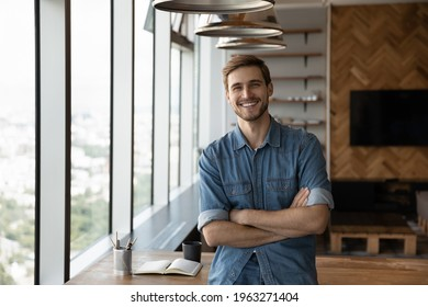 Portrait of smiling young successful Caucasian businessman stand pose in modern office show leadership. Happy man employee or worker feel motivated confident at workplace. Recruitment concept.