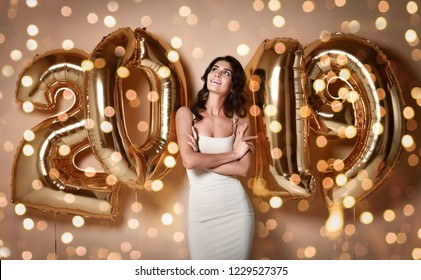 Portrait of a smiling young surprised girl in nude dress showing gift box and looking at camera Under boke Having Fun With Gold 2019 Balloons