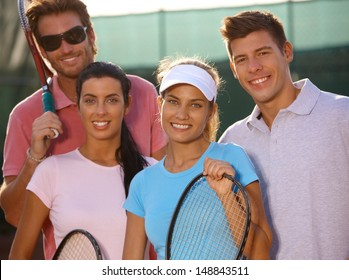 Portrait of smiling young tennis team on tennis court.