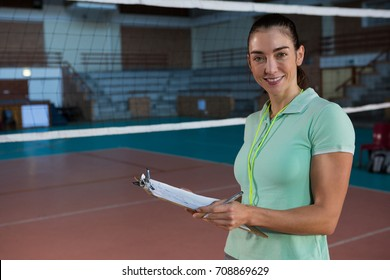 Portrait of smiling young volleyball coach holding clipboard at court