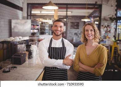 Portrait of smiling young wait staff standing with arms crossed by counter in coffee shop