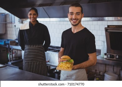 Portrait of smiling young waiter with coworker holding food tray in cafe