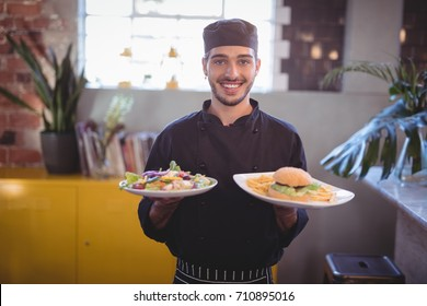 Portrait of smiling young waiter serving fresh food at coffee shop