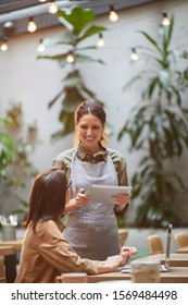 Portrait of smiling young waitress holding digital tablet while taking orders at outdoor cafe terrace lit by warm sunlight