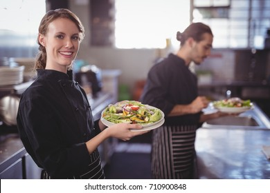 Portrait of smiling young waitress holding fresh salad against waiter at commercial kitchen in coffee shop