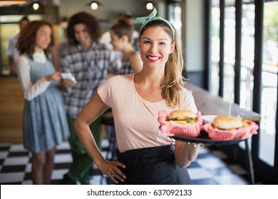 Portrait of smiling young waitress serving burger with customers in background at restaurant