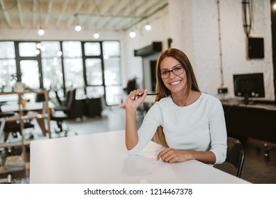 Portrait of a smiling young woman in bright co working office.
