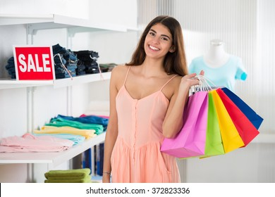 Portrait of smiling young woman carrying colorful shopping bags in clothing store