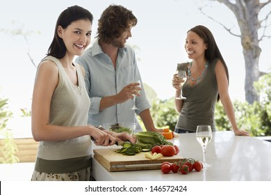 Portrait of smiling young woman chopping vegetables with friends communicating at kitchen counter