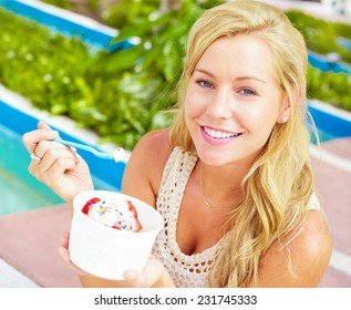 Portrait of smiling young woman eating frozen yogurt with strawberries in park