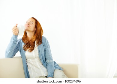 Portrait of a smiling young woman enjoying a caffee cup