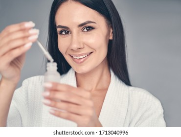 Portrait of a smiling young woman with a face serum looking in front of her