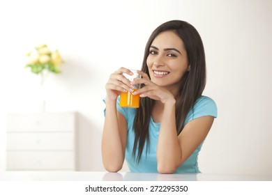 Portrait of smiling young woman with glass of orange juice at home