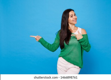 Portrait of smiling young woman in green casual clothes looking camera, pointing index fingers aside isolated on bright blue wall background in studio. People lifestyle concept. Mock up copy space