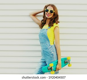 Portrait einer lächelnden jungen Frau mit grünem Skateboard auf weißem Hintergrund