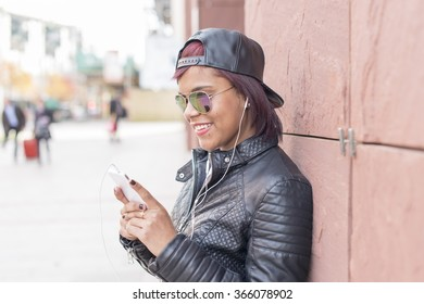 Portrait of smiling young woman with headphones and smart phone listening music in the street.