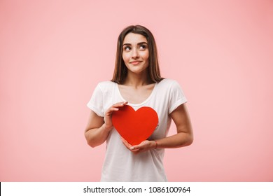 Portrait of a smiling young woman holding red heart isolated over pink background