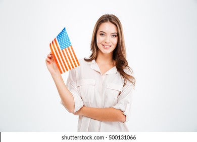 Portrait of a smiling young woman holding USA flag and looking at camera isolated on a white background