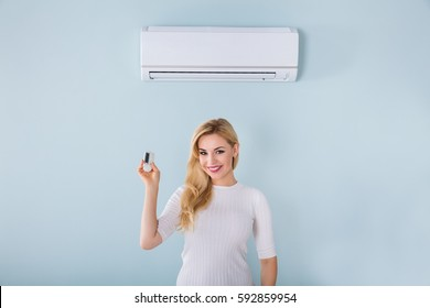Portrait Of Smiling Young Woman Holding Remote Controller Of Air Conditioner At Home