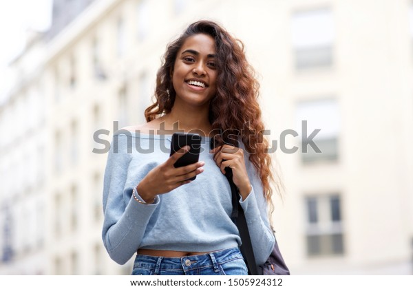 Portrait of smiling young woman holding mobile phone in city